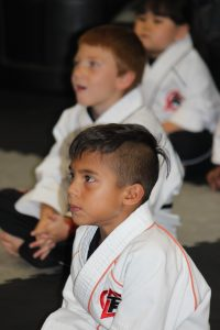 child in martial arts uniform sitting still and paying attention