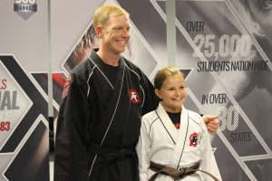 karate kid smiling from her success with instructor